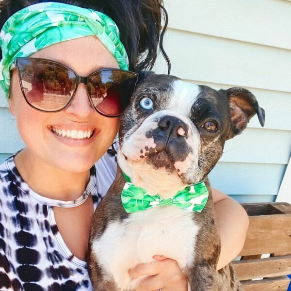 women in a headband holding a dog in a matching bow tie