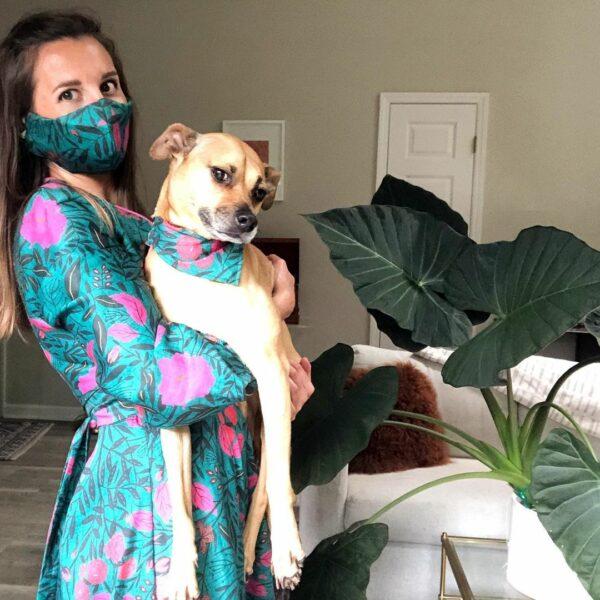 Women in a patterned dress wearing a matching mask and holding a dog wearing a matching bandana