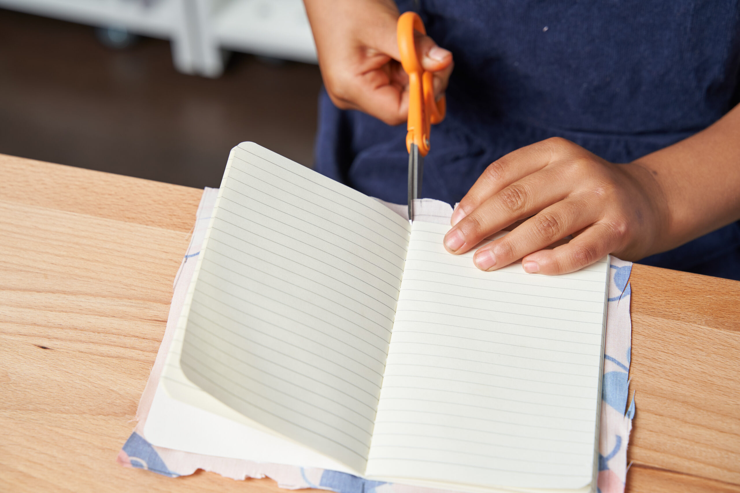 Scissors cutting small slits into the notebook fabric edges