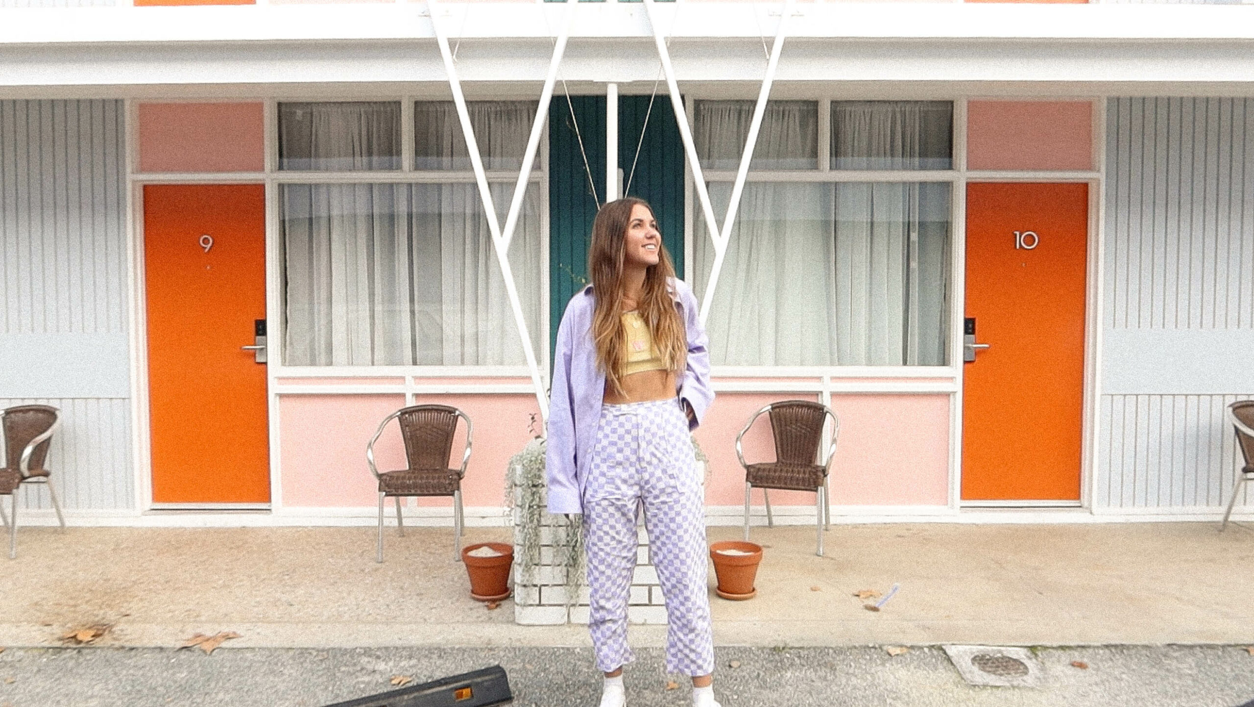 Maddy wears purple and white checkered pants in front of a retro building