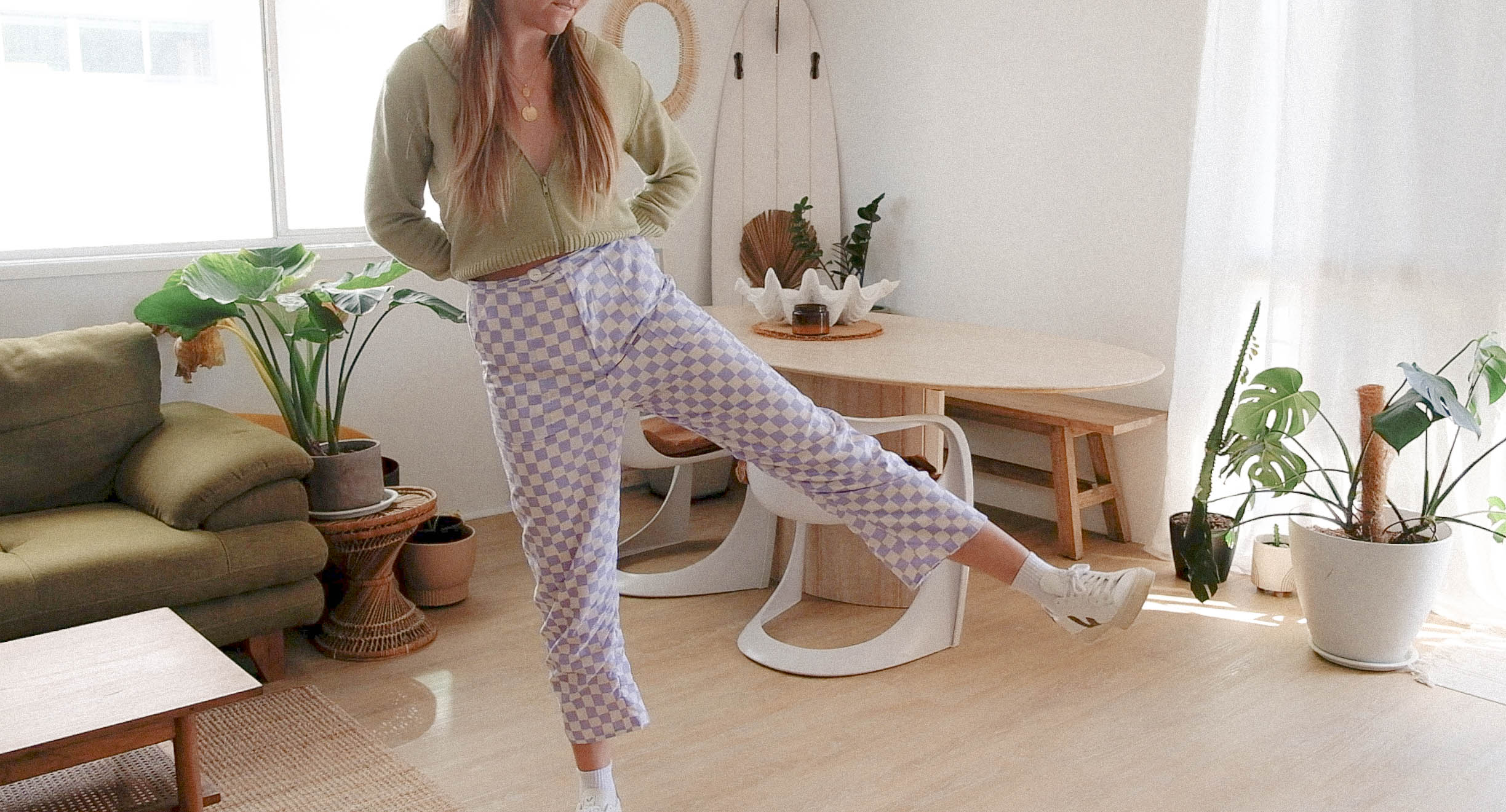 Maddy kicks her leg to the right while wearing white and purple checkered pants