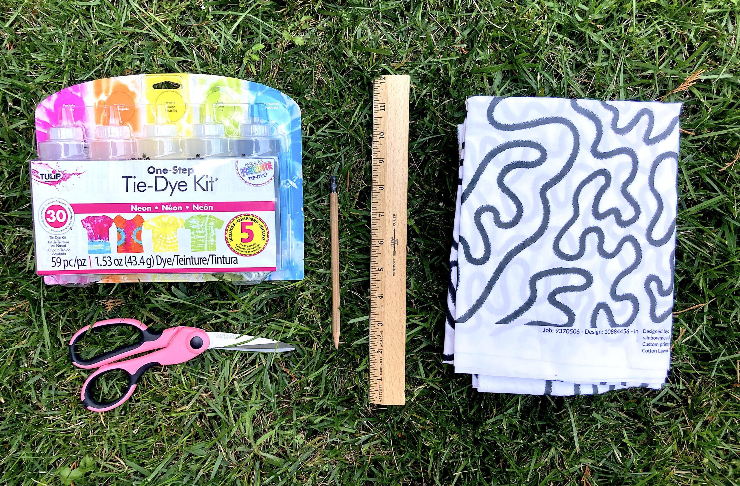 Tie-die bandana supplies: a tie-dye kit, scissors, a pencil, a ruler, and fabric