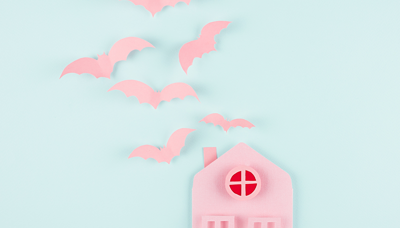 Pastel pink cutout of a haunted house with bats
