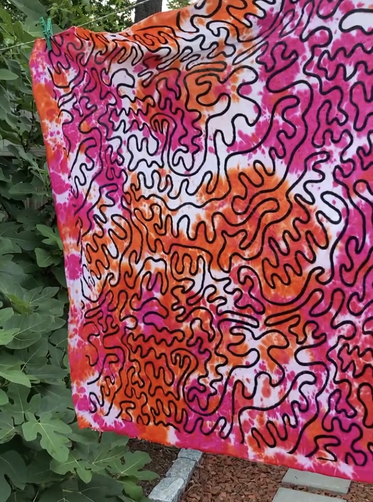 Pink and orange tie dyed fabric hanging
