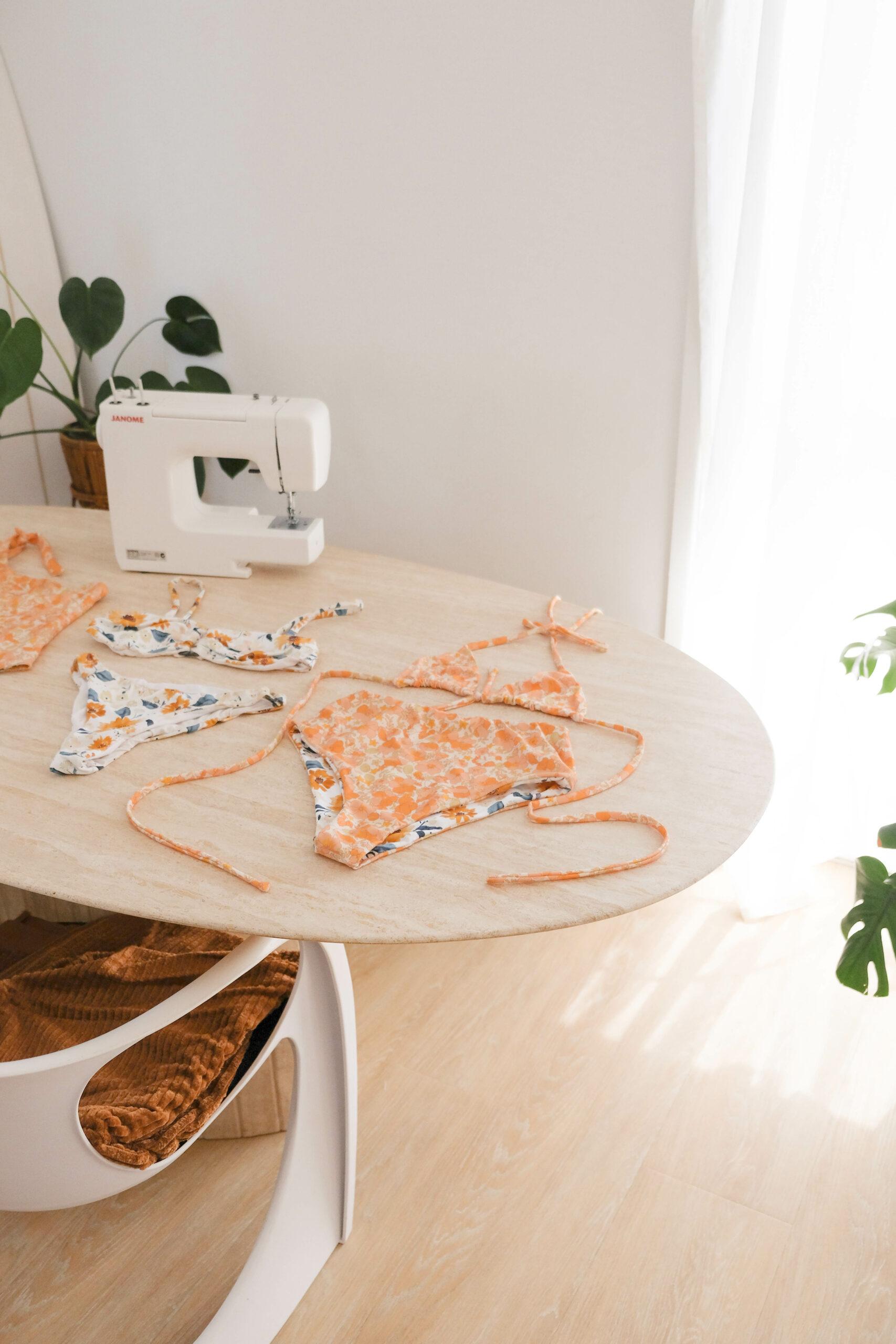 A reversible handmade bikini on a table near a sewing machine