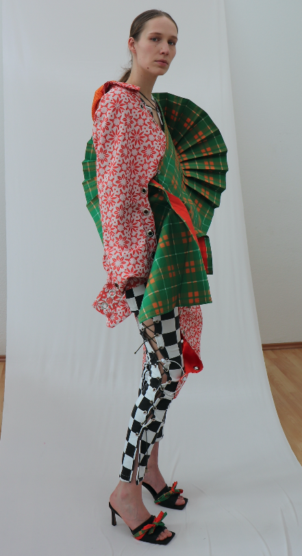 Model wearing outfit with pleated green fabric, a floral top and checkered pants