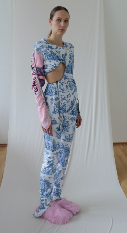 Model wearing blue and white bodysuit with pink sleeve and slippers