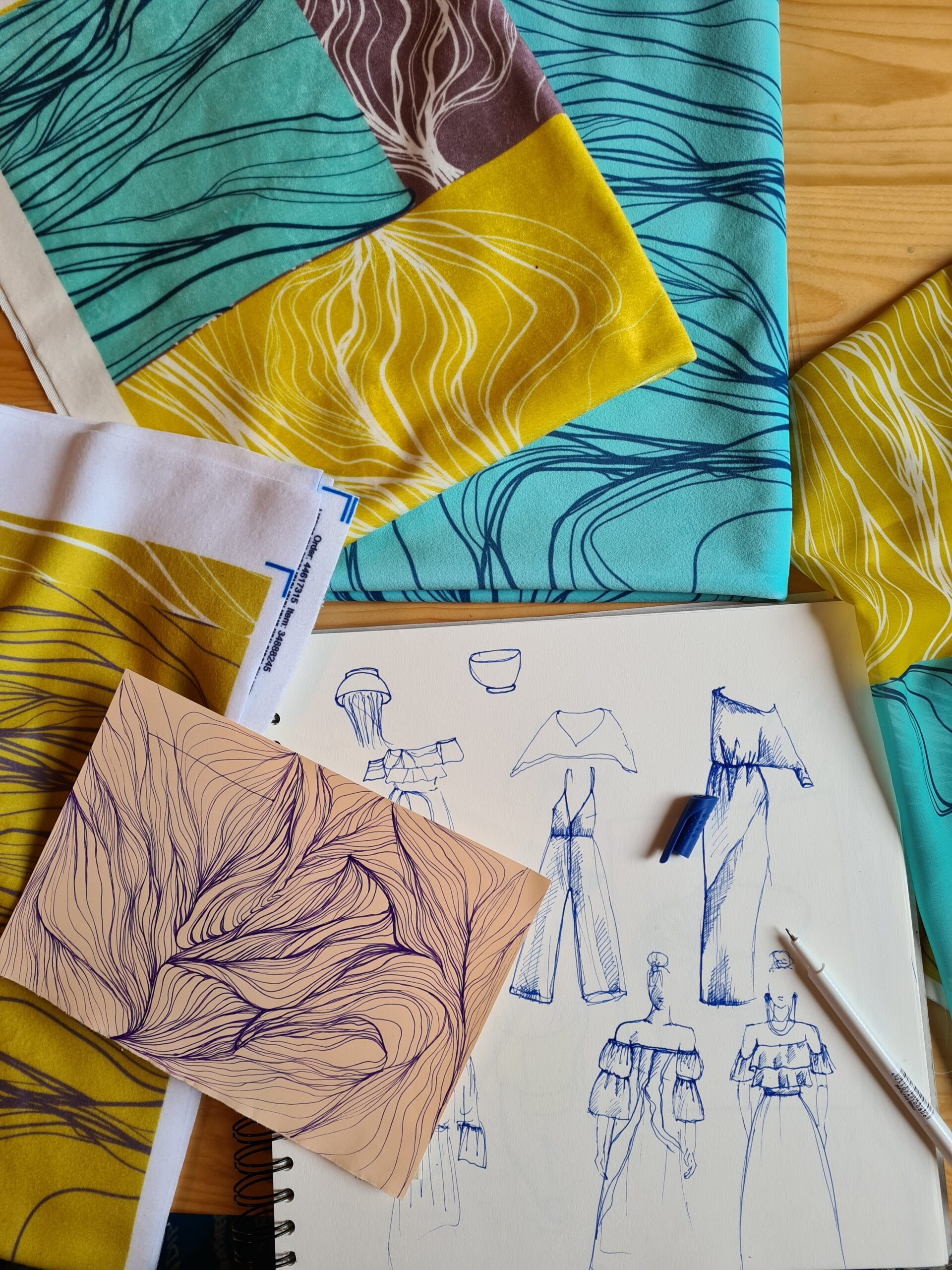Blue and green fabric designs on the floor with fashion sketches