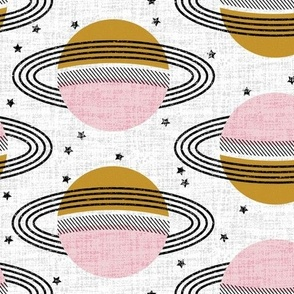 Fabric design with two repeating columns of planets. One column has planets with dark yellow tops and pink bottoms with a teal stripe in the middle and three black rings around them. The other column features planets with a pink top half and a yellow bottom half with a teal stripe in the middle and three black rings around it. All planets are floating on a white background with small black stars.