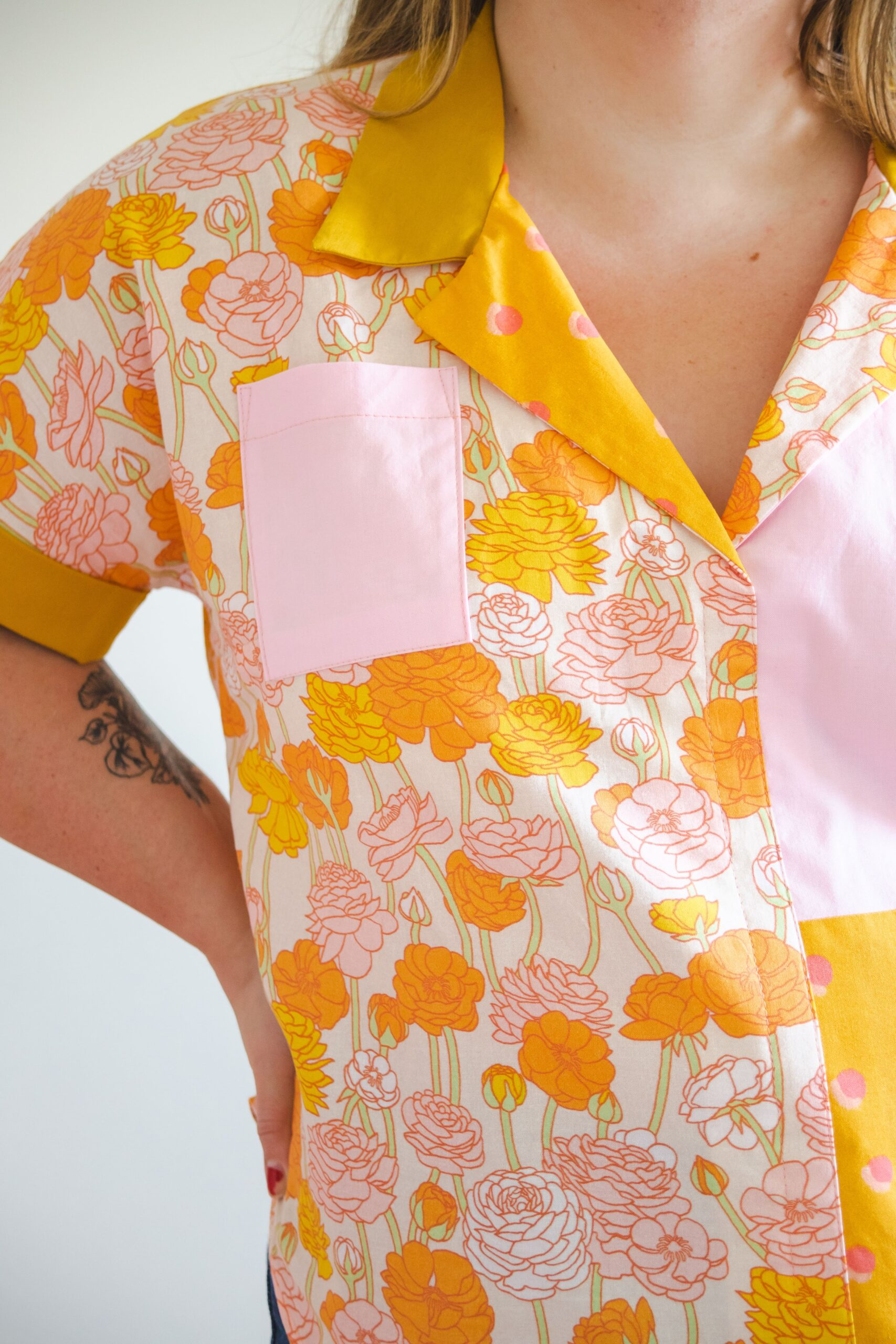 Close up of Meg wearing a yellow and pink shirt with polka dots and suns