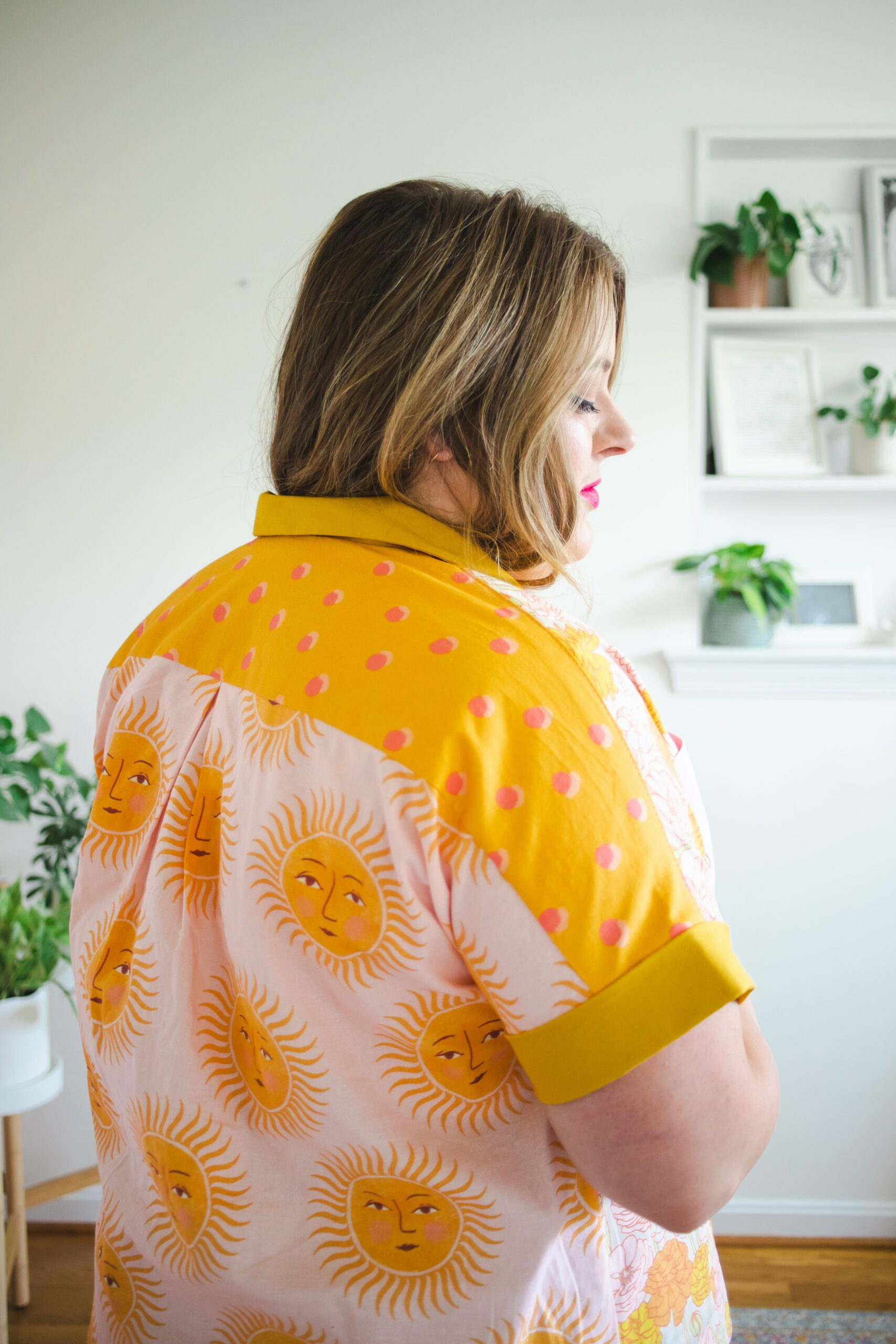 Meg wearing a yellow and pink shirt with polka dots and suns