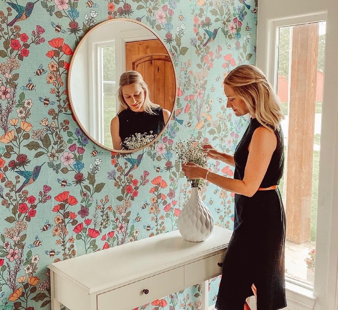 Floral wallpaper in an entryway with a mirror