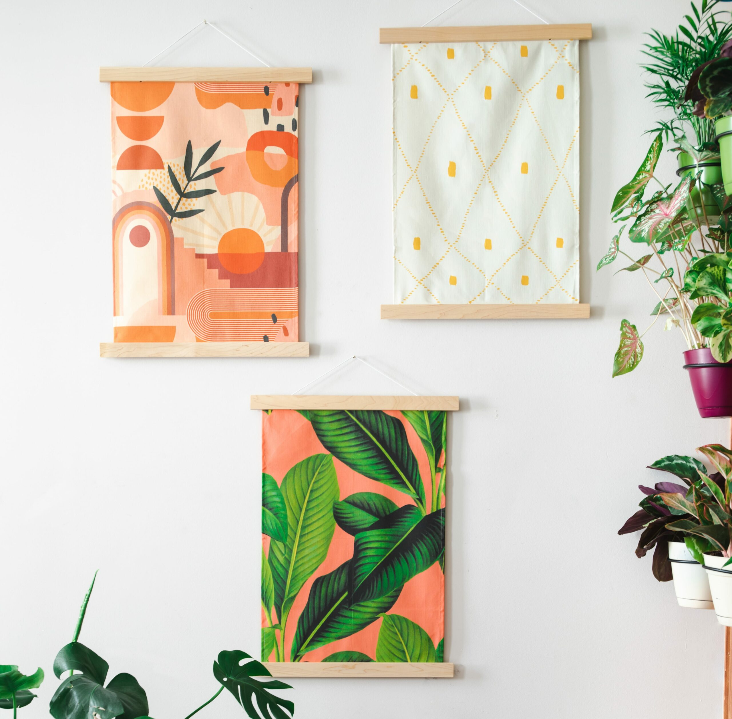 3 wall hangings with orange green and white designs