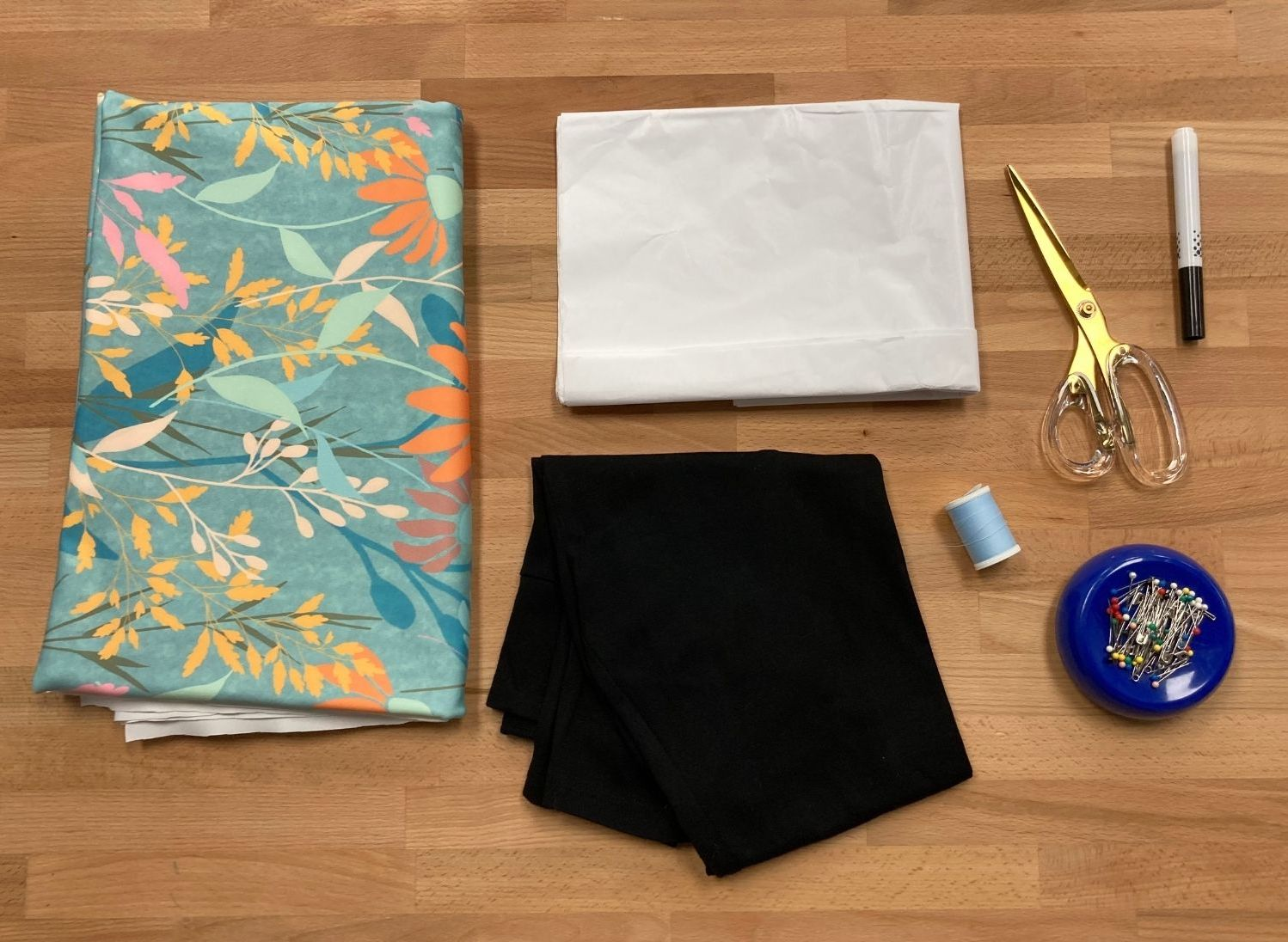 Supplies for leggings laying on table: Fabric, pattern paper, leggings, scissors, marker, thread and pins