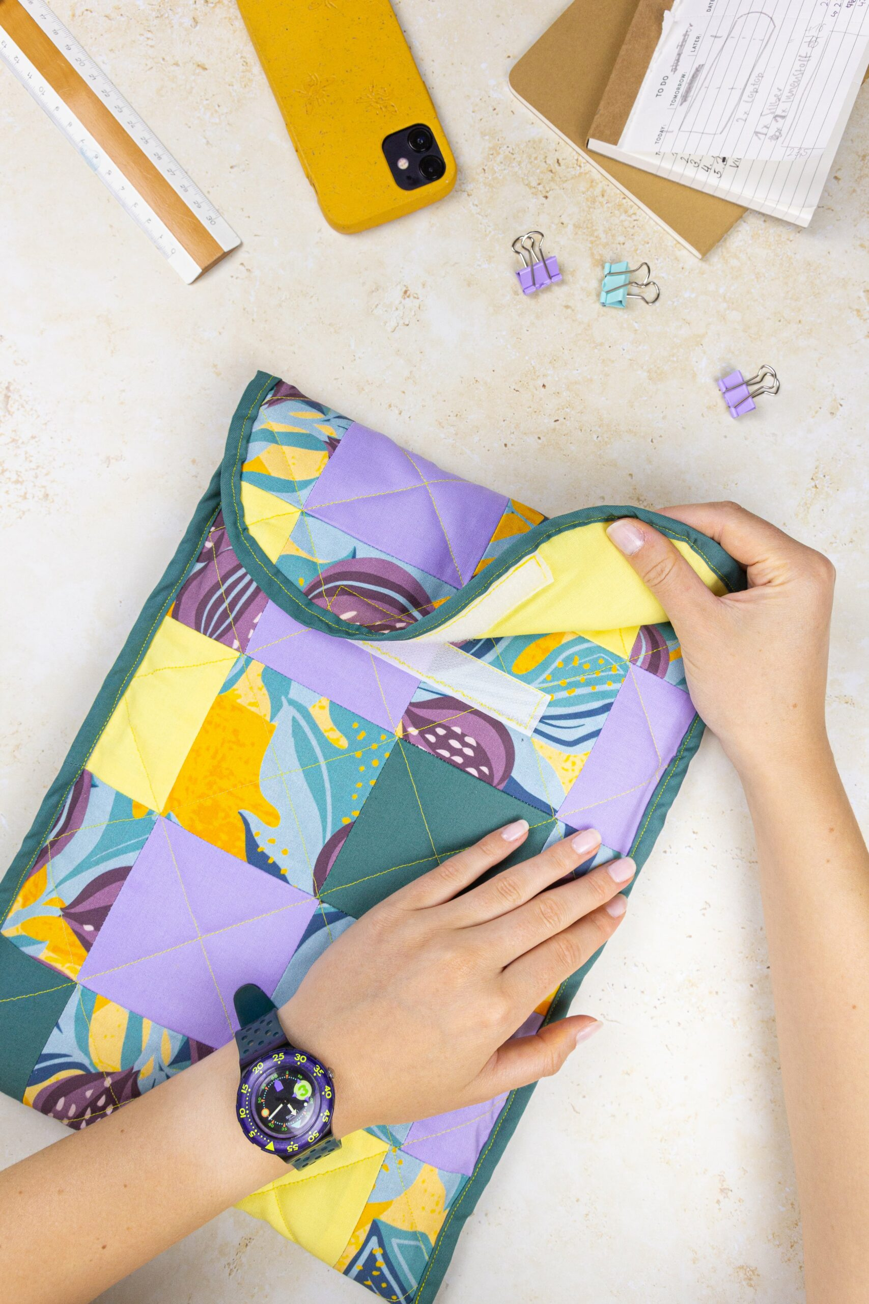 Opening a quilted laptop case, design is patchworked with lilac, pine, buttercup and other Spoonflower designs