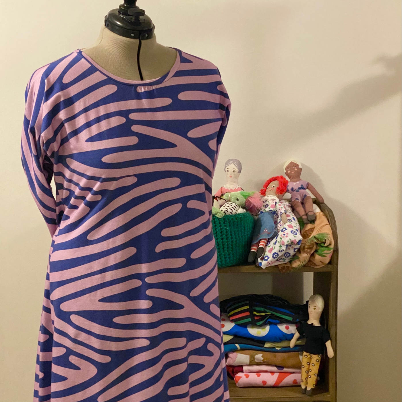 A blue dress with thick pink lines running through it is on a dress form
