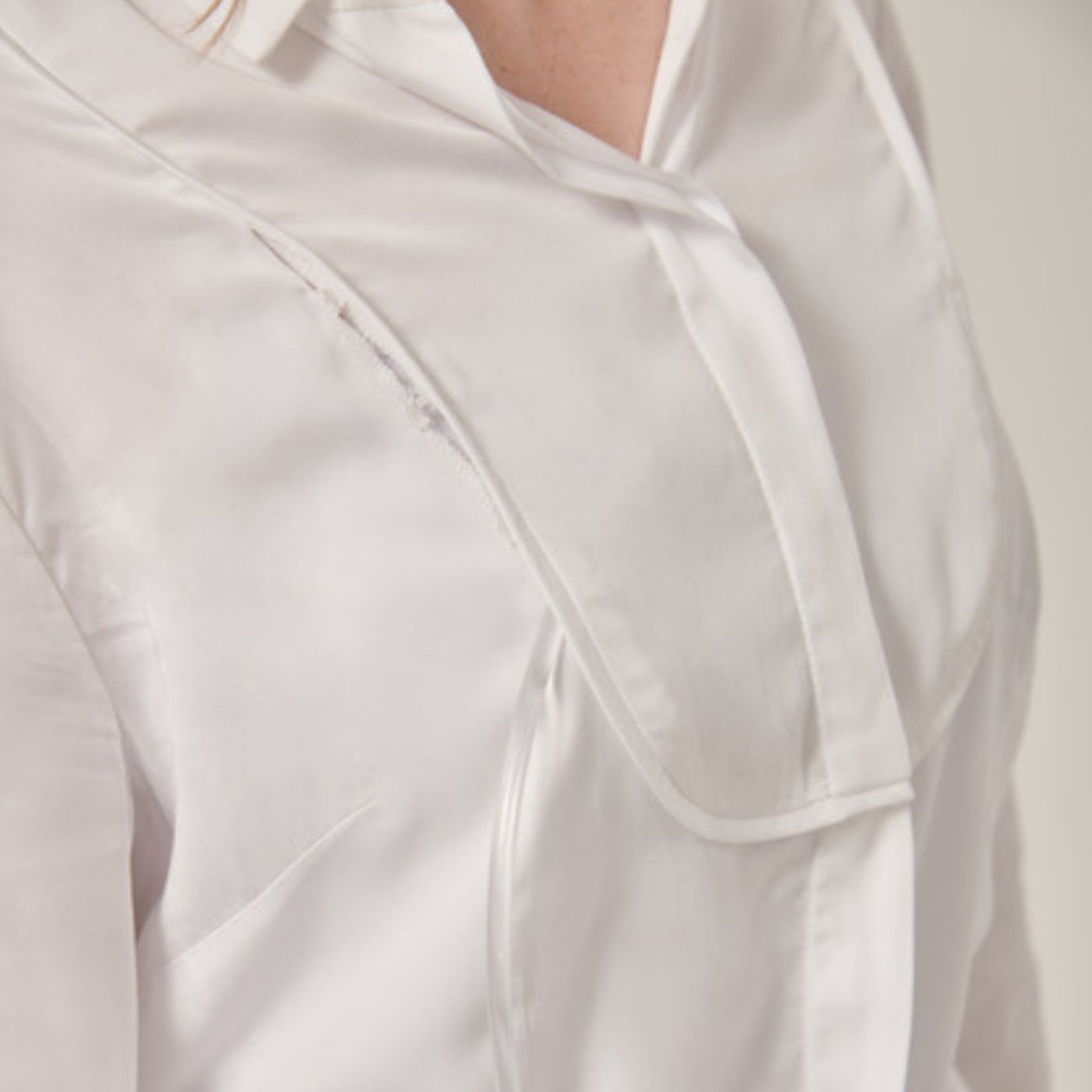 Torso of woman wearing a white button-up shirt. A clear medical tube is coming out from the bottom of the shirt and is concealed by piping up the shirt until it goes back under it above her chest.