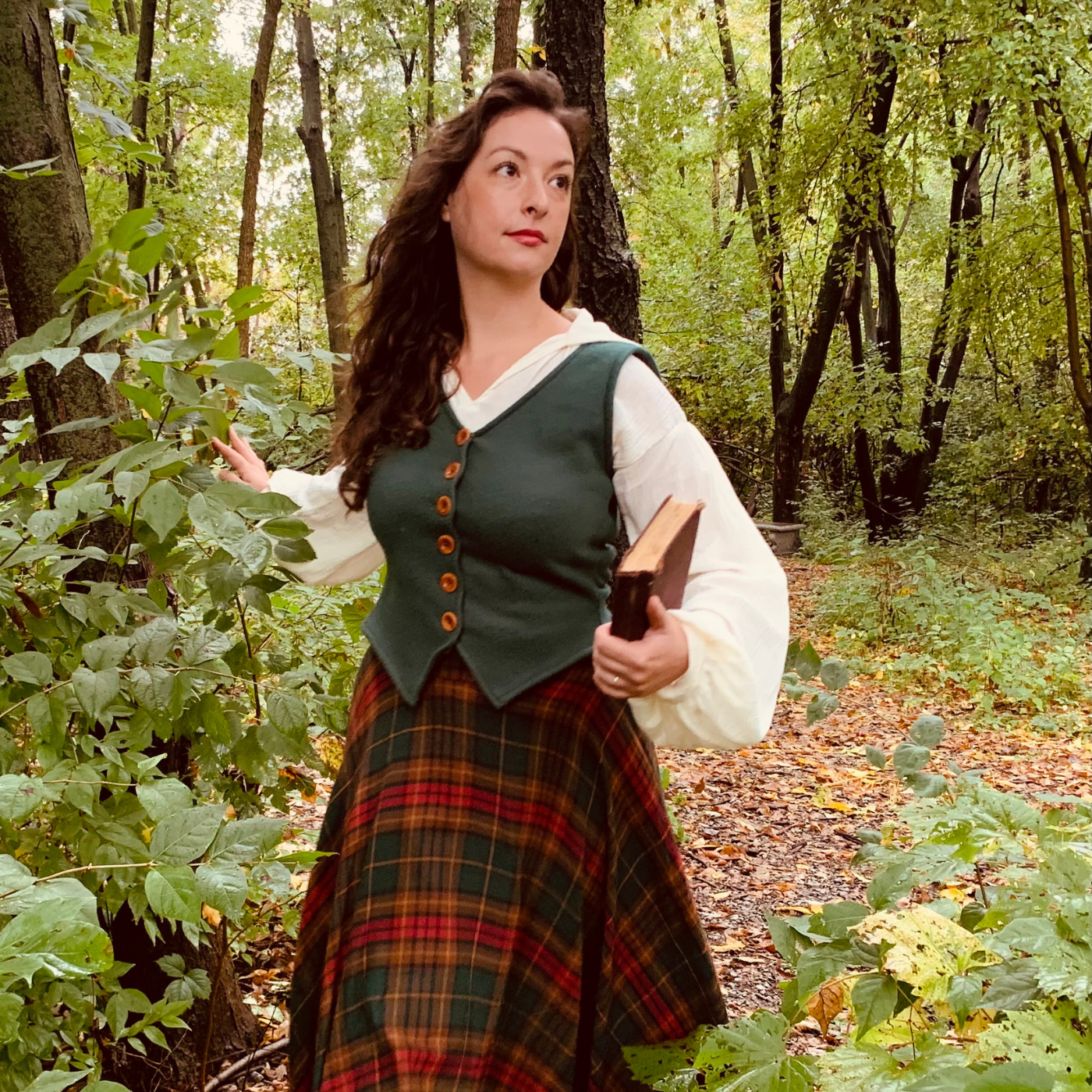 Fox is standing in the woods, wearing a long red-and-green plaid skirt, a dark green button-up vest and a cream long-sleeved shirt, holding a book in their left hand