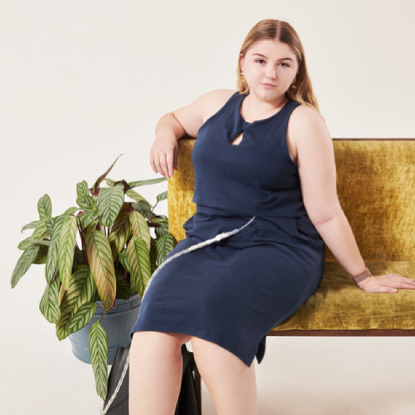 Charley-Anne Gordon is sitting on a dark yellow couch, looking at the camera, wearing a blue sleeveless dress from Unhidden Clothing.