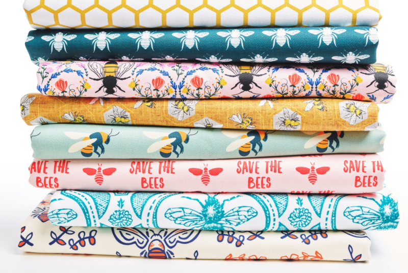 A stack of fabric designs relate to bees, from a large golden honeycomb design to mod and ant deco bees to a plea to save the bees.