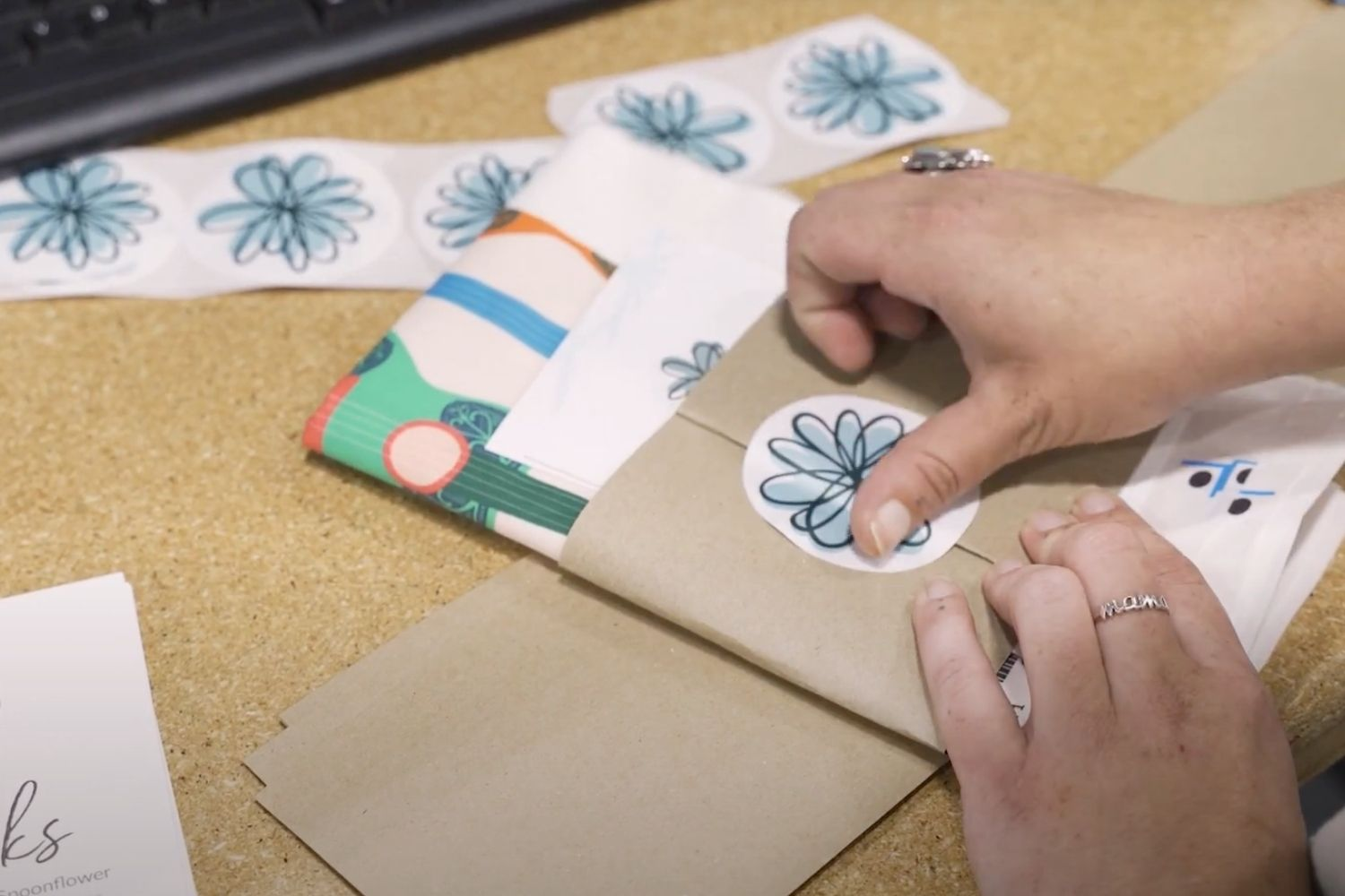 Placing a spoonflower sticker on top of packaging